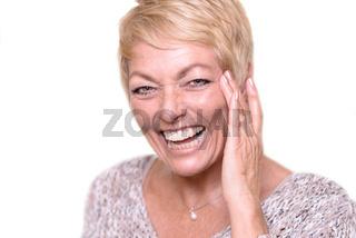 Lachende ältere Frau mit blonden Haaren
