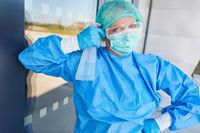 Reinigungskraft mit Desinfektionsmittel in Schutzkleidung vor Klinik Eingangsbereich