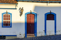Facade of old house in colonial architecture with blue windows and door