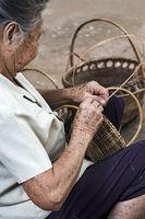 Gescvhickte Hände einer Fraum beim Korbflechten im Dorf Ban Done Keo, Laos