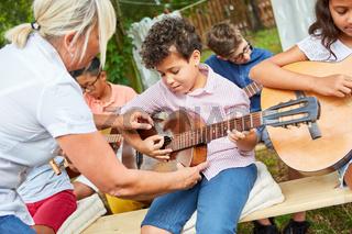 Lehrerin hilft Kind beim Gitarre spielen lernen