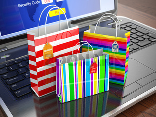 E-commerce concept. Colourful paper striped shopping bags on laptop keyboard.