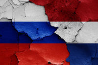 flags of Russia and Netherlands painted on cracked wall