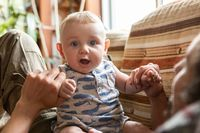 Playful baby sitting with father at home