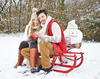 Paar im Winter trinkt Tee im Schnee