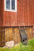Old wooden wheelbarrow on a farm wall
