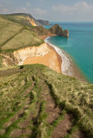 A high up view of the famous limestone arch Durdle Door and golden sand beach from the South West Coastal Path running on top of the near by cliffs