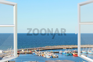 opened window with sea panorama and many boats are moored on pier on Baltic sea