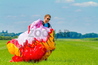 Paraglider carrying mattress flyer in green pasture