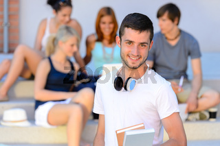 Happy student boy with books outside college