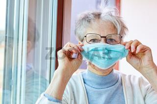 Seniorin in Quarantäne als Covid-19 Patientin mit Mundschutz