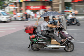 Man riding in a scooter on busy street in Chongqing