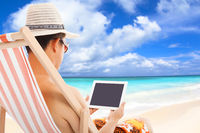 relaxed man sitting on beach chairs and touching tablet