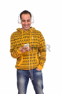 Mature happy Persian man using phone while listening to music