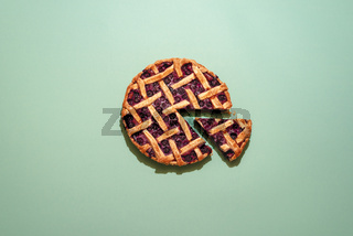 Blueberries pie with lattice crust top view on a green background.