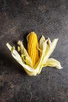 Uncooked corn cob on black table.