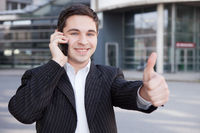 Manager mit Handy hält Daumen hoch