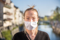COVID-19 pandemic coronavirus. Young girl in city street wearing face mask protective for spreading of coronavirus disease 2020. Close up of young woman with medical mask on face against SARS-CoV-2