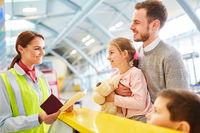 Servicekauffrau am Flughafen Check-In kontrolliert Pass