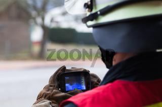 Feuerwehrmann bedient eine Waermebildkamera