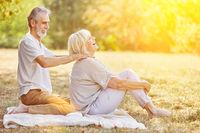 Mann massiert Nacken seiner Frau im Sommer