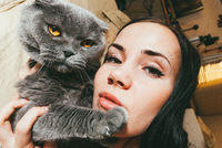 Beautiful young woman holds a cat in her arms and is bored at home quarantine. Stay at Home Fighting the coronavirus concept