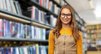 smiling teenage student girl in glasses at library