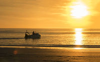 Western Australia – Silhouette of a boat at the sunset evening light on Cable Beach in Broome