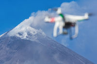 Flying drone quadcopter UAV aerial photography in sky on background volcano eruption. Focus on mountain peak
