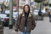 Young Caucasian Woman Smiling on Sidewalk Listening to Earphones