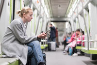 Portrait of lovely girl typing message on mobile phone in almost empty public subway train. Staying at home and social distncing recomented due to corona virus pandemic outbreak