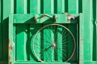 Vorderrad Felge an einem grünen Container als Hintergrund