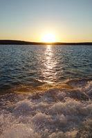 Lake sunset with boat wake waves