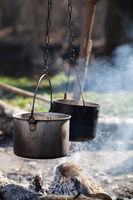 Two sooty old cauldrons on bonfire with smoke at forest