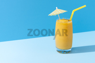 Mango smoothie with a cocktail umbrella. Summer cold drink