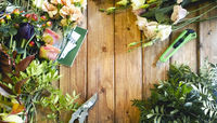 Various flowers and leaves with professional florist tools on wooden table