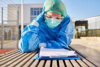 Pflegepersonal vor Klinik beim Studium von Liste zur Kontaktverfolgung
