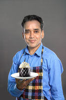 Indian Male Chef with a Sweet Dish Cake on grey Background