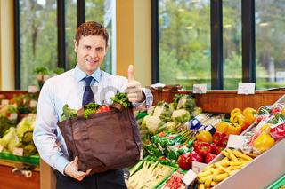 Mann mit Einkaufstasche hält Daumen hoch