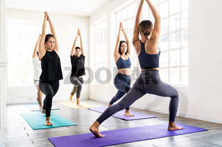Asian sporty people practicing yoga in Class