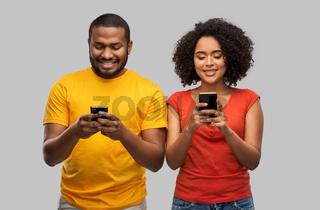 happy african american couple with smartphones