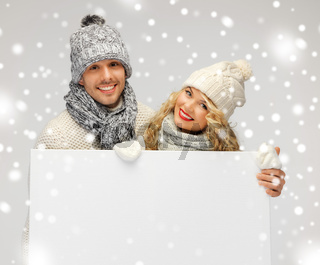 couple in a winter clothes holding blank board