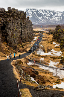 Tourist people walking at the Thingvellir national park in Iceland in spring.
