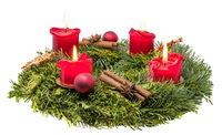 Verzierter Adventskranz aus Tannenzweigen mit brennenden roten Kerzen