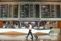 Singapur, Republik Singapur, Pilot vor Anzeigetafel mit Fluginformationen am Flughafen Changi