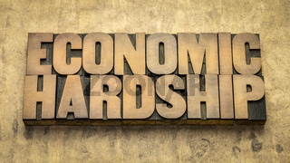 economic hardship word abstract in  wood type