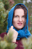 Portrait of brunette standing in pine forest. Woman dressed in brown pullover, blue scarf thrown over head