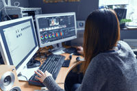 The Brunette Is Carefully At The Monitor Of Her Computer And Working In A Video Processing Program
