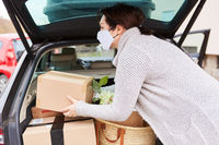 Frau mit Mundschutz packt Kofferraum mit Paketen