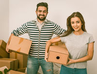 Young couple smiling and holding boxes while standing among unpacked boxes